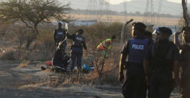 Police medics tend to a wounded miner injured during clashes between protesting miners and police near a platinum mine in Marikana, South Africa, on August 16, 2012.  By  (AFP/File)