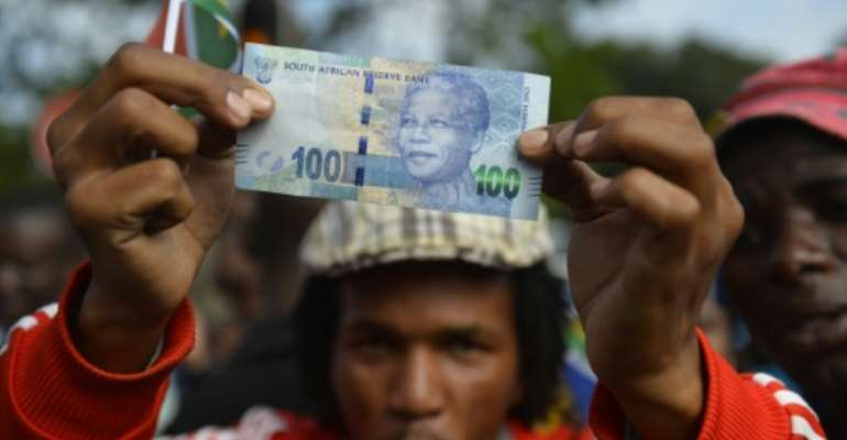 The rand broke through the 13 rand resistance level against the dollar before midday, extending its loss in value this year to 11 percent.  By Odd Andersen (AFP/File)