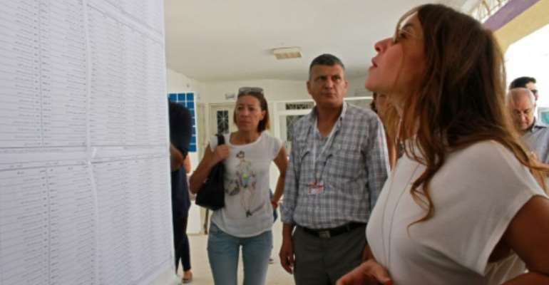 Salwa Smaoui, wife of jailed Tunisian presidential candidate Nabil Karoui, looks for her name before casting her ballot on Sunday.  By MOHAMED KHALIL (AFP)