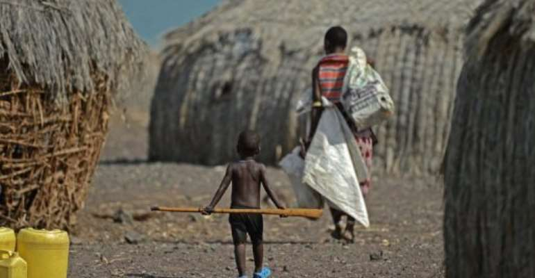 A mother and child walk in the village of Komote on the shores of Lake Turkana, northern Kenya on May 18, 2012.  By Carl de Souza (AFP/File)