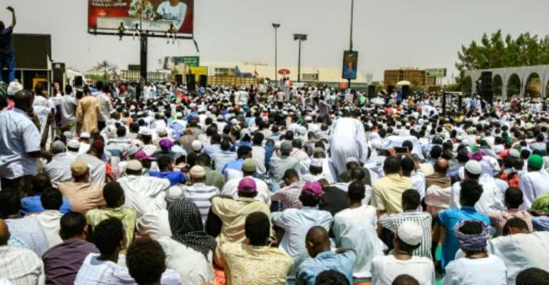 Scores attend Friday prayers outside the army headquarters in Khartoum as they demand that a military council makes way for civilian rule after the ousting of Omar al-Bashir.  By Ebrahim Hamid (AFP)