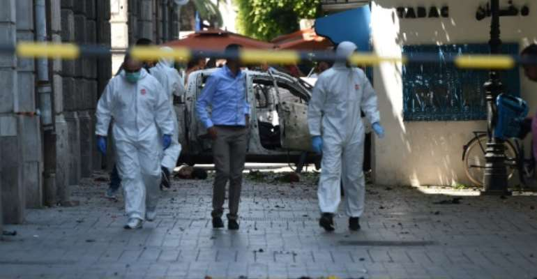 Security and investigative personnel near a shrapnel riddled vehicle at the scene of a suicide bombing in Tunis on Thursday.  By FETHI BELAID (AFP)
