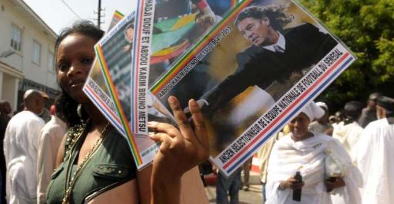 A woman sells pictures of late French coach Bruno Metsu during his burial on October 21, 2013 in Dakar.  By Seyllou (AFP)