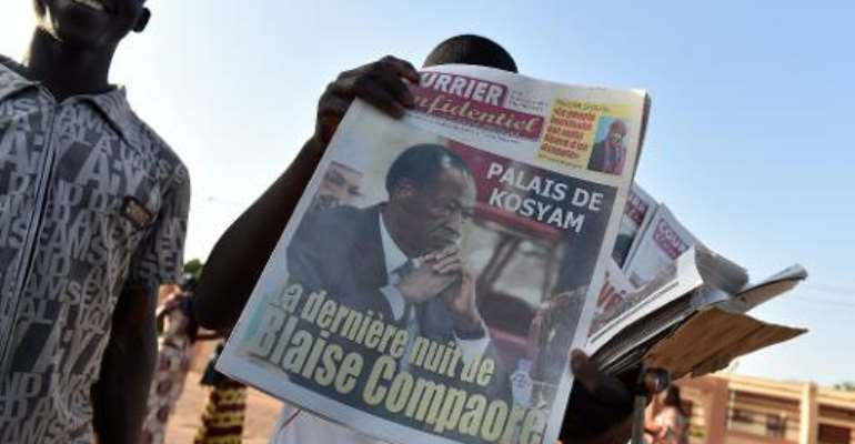 A man sells newspapers in a street of Ouagadougou on November 11, 2014, with headlines regarding the ouster of former president Blaise Compaore.  By Issouf Sanogo (AFP)