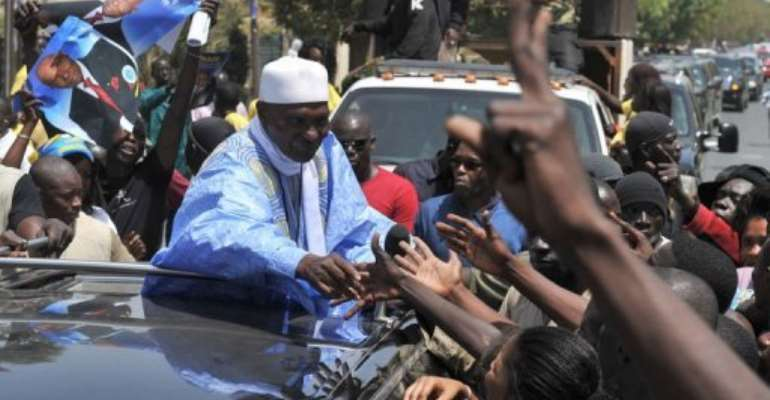 Senegalese President and presidential candidate Abdoulaye Wade greets supporters.  By Issouf Sanogo (AFP)