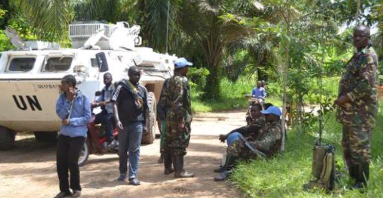 UN peacekeepers of the MONUSCO force stand next to a UN vehicle, after the bodies of seven people were found on May 9, 2015 in Matembo, in the Democratic Republic of Congo's North-Kivu province.  By Kudra Maliro (AFP)
