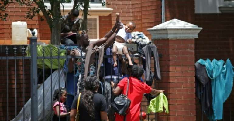 Several hundred asylum-seekers scaled the iron railings of the  United Nations High Commissioner for Refugees office in Pretoria seeking protection.  By Phill Magakoe (AFP)