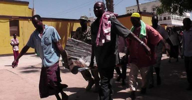Rescuers shift a victim on November 19, 2013, following an attack by Somalia's Shebab suicide commandos in the central Somali town of Beledweyne, claimed by the Al-Qaeda-linked Shebab.  By  (AFP)