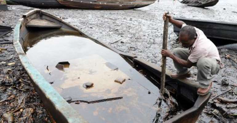 An indigene of Bodo, Ogoniland region in Rivers State, tries to separate with a stick the crude oil from water in a boat at the Bodo waterways polluted by oil spills attributed to Shell equipment failure August 11, 2011.  By Pius Utomi Ekpei (AFP/File)