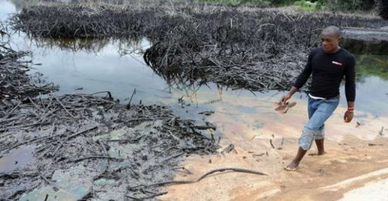 A man walks near spilled crude oil in the waters of the Niger Delta swamps of Bodo, a village in the famous Nigerian oil-producing Ogoniland, which hosts the Shell Petroleum Development Company, on June 24, 2010.  By Pius Utomi Ekpei (AFP/File)