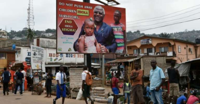 People walk under an Ebola's information board featuring Sierra Leone's president Ernest Bai Koroma on January 22, 2016 in a street of Freetown..  By Sia-Kambou (AFP/File)