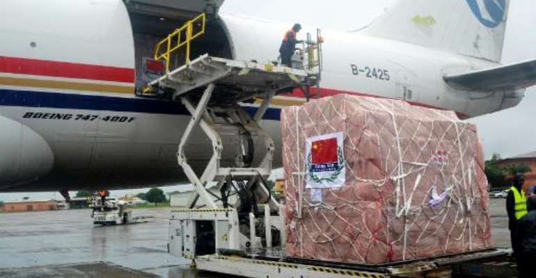 Workers unload medical supplies from China for countries hit by the Ebola outbreak at the Conakry airport on August 11, 2014.  By Cellou Binani (AFP/File)