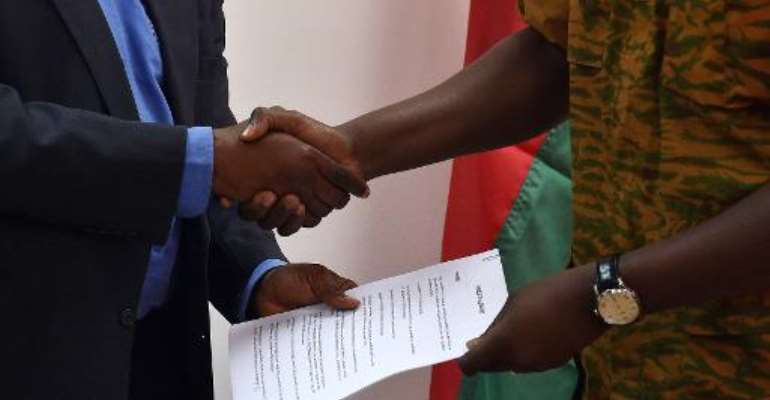 Henry Ye, president of the commission representing the main power players, hands the transition charter to Burkina Faso's army-appointed leader, Lieutenant-Colonel Isaac Zida during a meeting in Ouagadougou on November 14, 2014.  By Issouf Sanogo (AFP)
