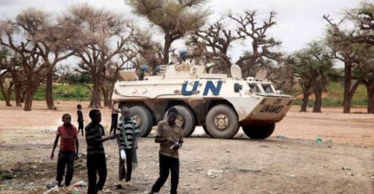 Sudanese boys walking past a UNAMID armoured personnel carrier patrolling Kutum in North Darfur.  By Albert Gonzalez Farran (AFP/UNAMID/File)