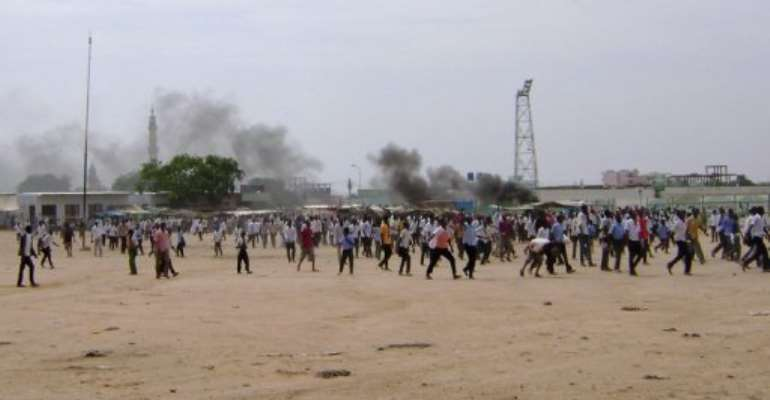 Smoke billows from burning tyres as Sudanese demonstrators protest against rising prices.  By  (AFP)