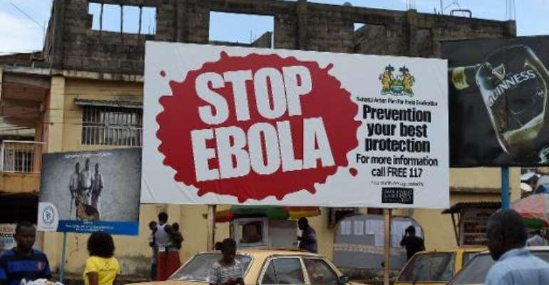 People walking past a billboard reading