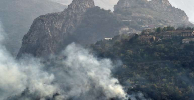 Smoke billows as a fire burns woodland by a mountain town in the Ait Daoud area of northern Algeria in this picture taken on August 13, 2021.  By RYAD KRAMDI (AFP/File)