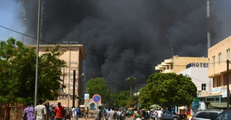 Smoke rises from the Burkinabe capital Ouagadougou from a jihadist attack in March 2018. Eight  soldiers and eight assailants died, according to an official toll.  By Ahmed OUOBA (AFP/File)