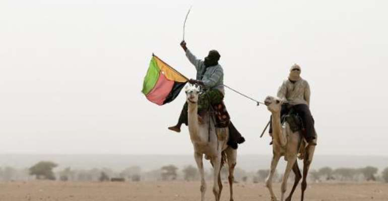 A Tuareg man holds the flag of the National Movement for the Liberation of Azawad during a demonstration in support of the MLNA on July 28, 2013 in Kidal, northern Mali.  By Kenzo Tribouillard (AFP/File)