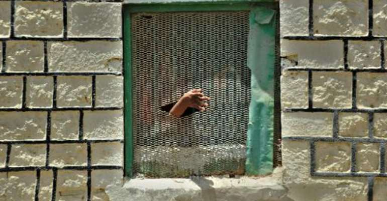 File picture taken on March 30, 2011 shows an inmate pushing his hand out through a hole on a window grille at the Berbera prison in Somalia's breakaway republic of Somaliland.  By Tony Karumba (AFP/File)