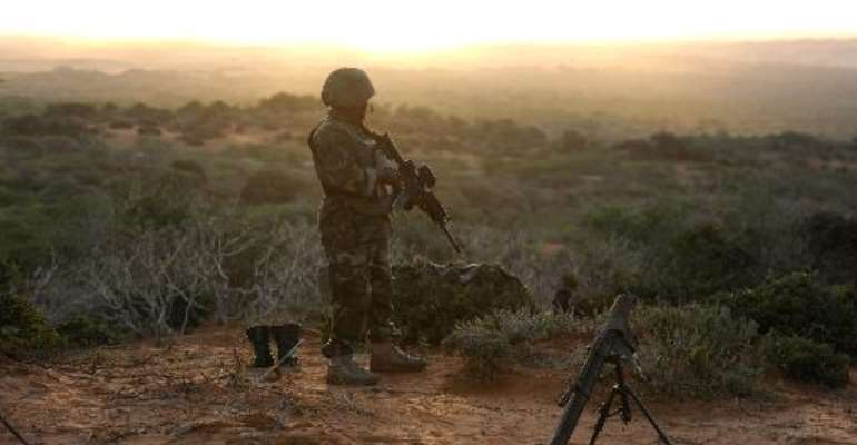 Handout image made by the African Union Mission to Somalia on October 6, 2014, shows a soldier belonging to the African Union Mission in Somalia, standing on the top of a hill next to the al-Shabab stronghold of Barawe.  By Tobin Jones (AMISOM/AFP/File)