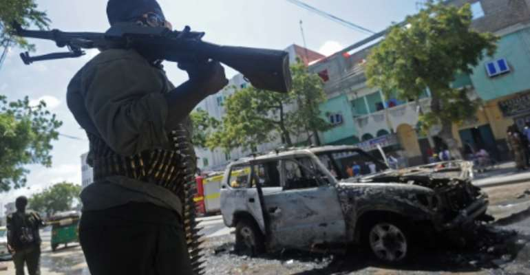 Somali soldiers guard the burnt-out wreckage of a car that was targetted in a bomb attack in Mogadishu, on September 5, 2016.  By Mohamed Abdiwahab (AFP/File)