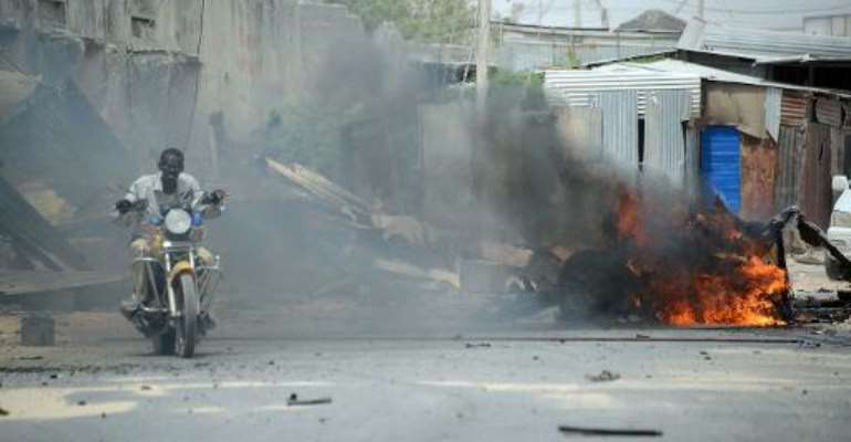 A man rides a motorbike past a burning car shortly after it exploded on February 13, 2014 near the entrance of Mogadishu's  international airport.  By Mohamed Abdiwahab (AFP)
