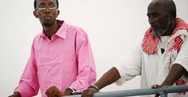 Somali journalist Abdiaziz Abdinuur (L) is pictured in court in Mogadishu on February 5, 2013.  By Mohamed Abdiwahab (AFP/File)