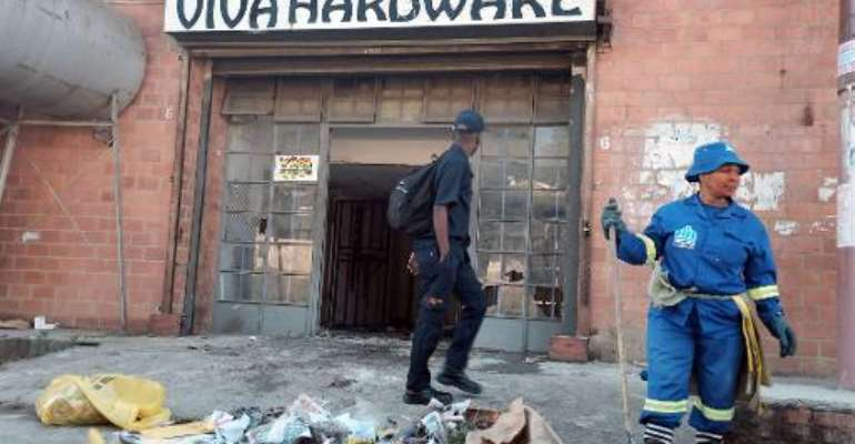 A worker from the eThekwini municipality cleans up after a xenophobic attack on a Somali businesses in Umlazi township, south of Durban, on April 10, 2015.  By Rajesh Jantilal (AFP)