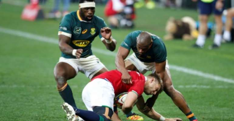 South Africa skipper and flanker Siya Kolisi (L) and winger Makazole Mapimpi (R) try to dispossess British and Irish Lions scrum-half Conor Murray during the second Test in Cape Town last weekend.  By PHILL MAGAKOE (AFP)
