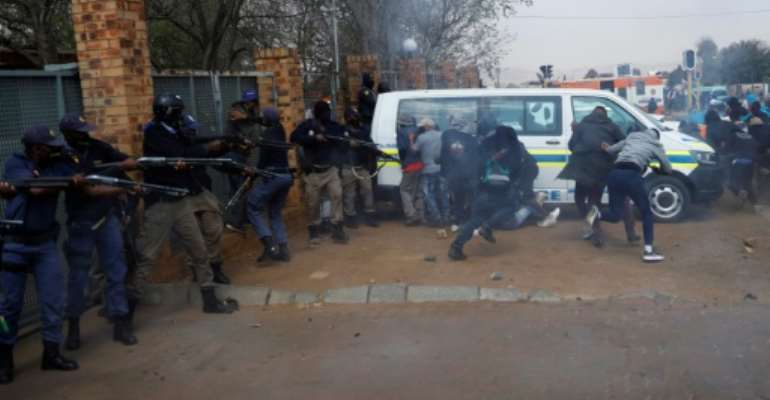 South African police officers fired tear gas and rubber bullets at protesters in a Johannesburg suburb.  By Michele Spatari (AFP)