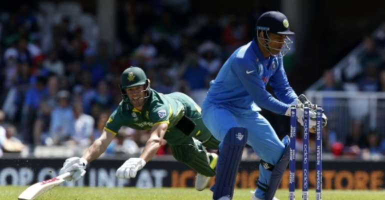 South Africa's AB de Villiers (left) is run out as India's MS Dhoni stumps the wicket during their ICC Champions Trophy match at The Oval in London on June 11, 2017.  By Ian KINGTON (AFP)