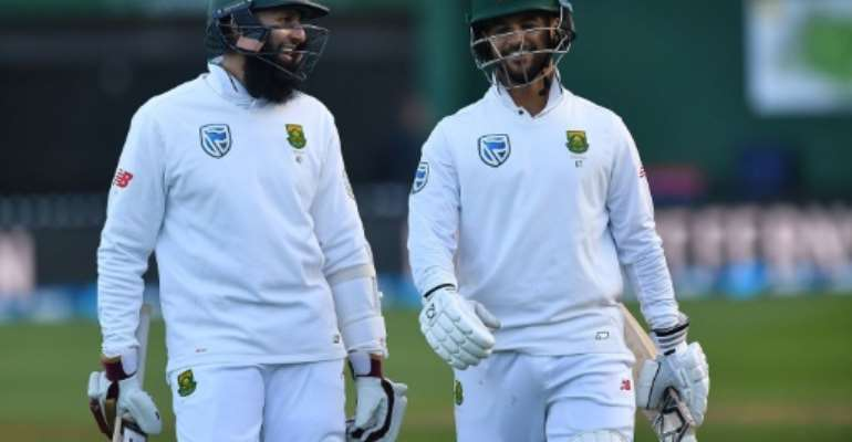 South Africa's Hashim Amla (L) and Jean-Paul Duminy celebrate after winning their 2nd Test against New Zealand, at the Basin Reserve in Wellington, on March 18, 2017.  By Marty Melville (AFP)