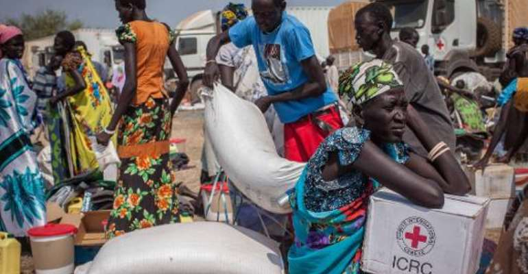 People receive food aid and other vital supplies on January 8, 2014 from the International Committee of the Red Cross, in Minkaman, South Sudan.  By Nichole Sobecki (AFP/File)