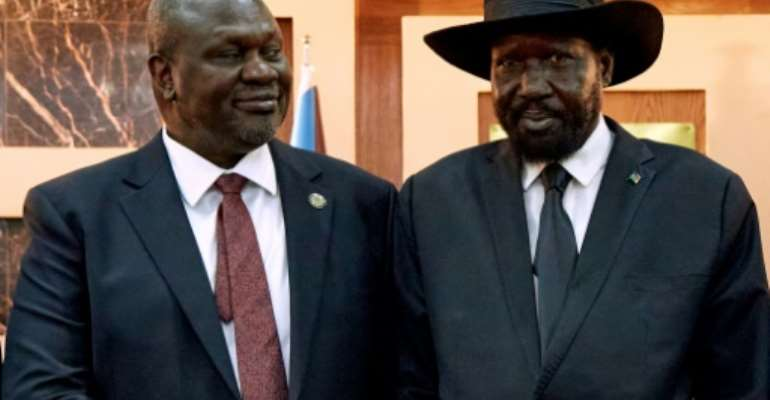 South Sudanese President Salva Kiir (R) shakes hands with First Vice President Riek Machar in 2020.  By ALEX MCBRIDE (AFP)