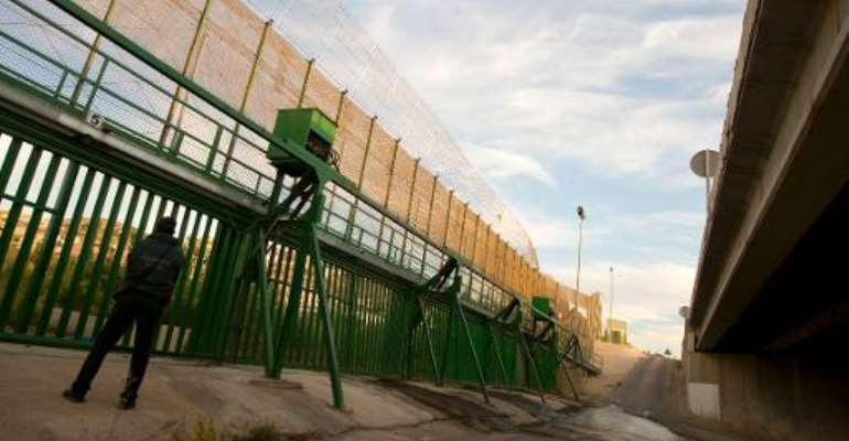 A member of the Guardia Civil stands next to the border fence between Spain and Morocco in Melilla on October 17, 2013.  By Pierre-Philippe Marcou (AFP/File)