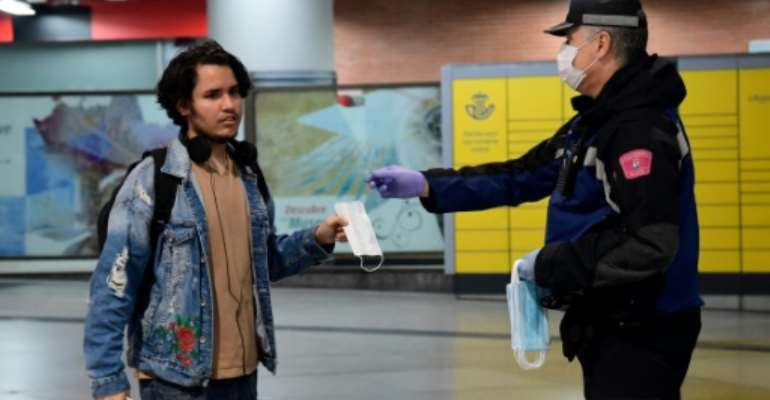 Spanish police officers handed out face masks to commuters as lockdown restrictions eased Monday.  By JAVIER SORIANO (AFP)