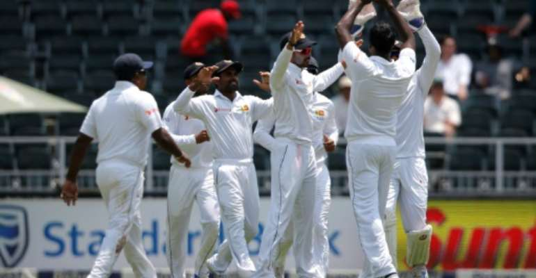 Sri Lanka celebrate the wicket of South Africa opening batsman Dean Elgar (not shown) during the third Test at Wanderers Cricket Stadium in Johannesburg on January 12, 2017.  By Marco LONGARI (AFP)