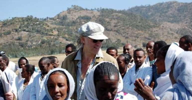 A picture taken on November 25, 2009, shows founder of the Band Aid charity Bob Geldof (C) with local people during a visit to Korem in Ethiopia.  By Aaron Maasho (AFP/File)