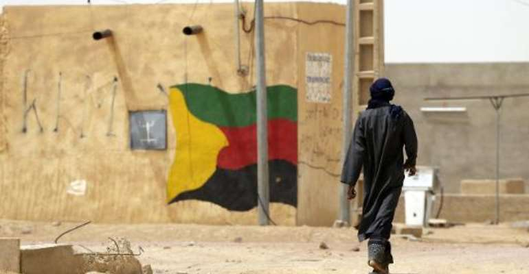 This picture taken on July 27, 2013 shows a man walking past a flag of the National Movement for the Liberation of Azawad (MNLA) painted on a wall in Kidal.  By Kenzo Tribouillard (AFP/File)