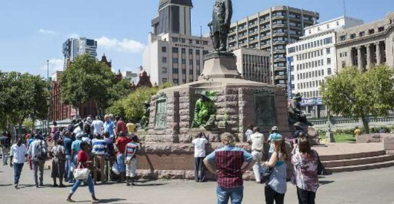 People visit the defaced statue of Paul Kruger in Church Square, Pretoria on April 6, 2015.  By Stefan Heunis (AFP)