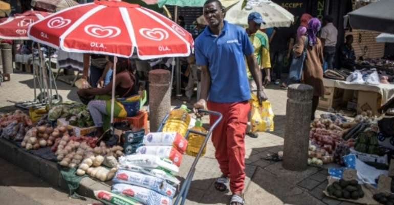 Stocking up: South Africans have rushed to buy long-life food and milk, snacks and toilet paper ahead of a three-week lockdown.  By MARCO LONGARI (AFP)