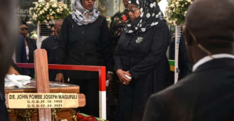 Succession: New Tanzanian President Samia Suluhu Hassan, right, before the coffin of her predecessor, John Magufuli, who died in mysterious circumstances in March.  By STR (AFP)