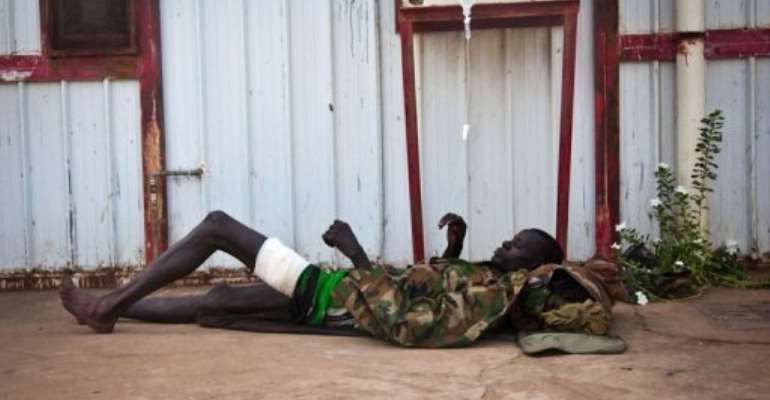 A wounded soldier of the South-Sudan's Sudan People's Liberation Army (SPLA) rests outside the Rubkona Military Hospital.  By Adriane Ohanesian (AFP)