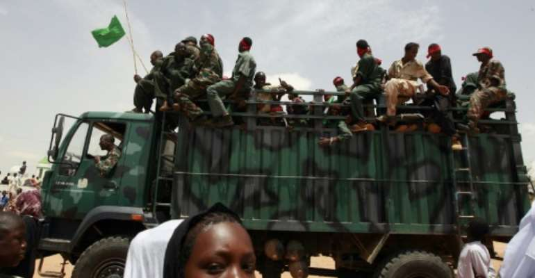 A Sudanese girl walks past a truck carrying soldiers in the West Darfur state capital of El Geneina on July 24, 2008.  By Khaled Desouki (AFP/File)