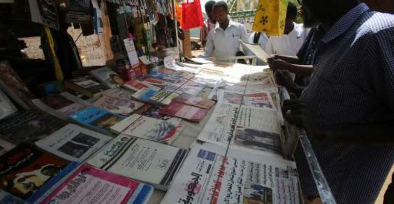 Sudanese men look at newspapers displayed at a kiosk in the capital Khartoum on February 16, 2015.  By Ashraf Shazly (AFP)