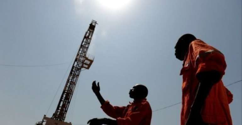 Two workers stand in the Unity oil field in South Sudan.  By Roberto Schmidt (AFP/File)