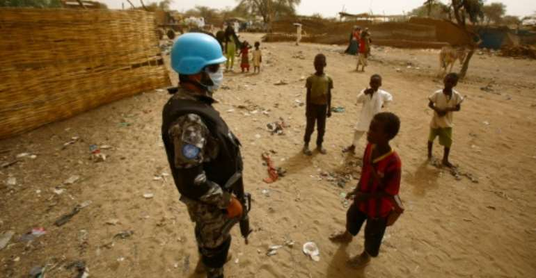 Sudanese children stand next to a member of the UN-Afrcian Union mission in Darfur (UNAMID), a mission that expects significant troop cuts under a proposal for strategic review.  By ASHRAF SHAZLY (AFP/File)