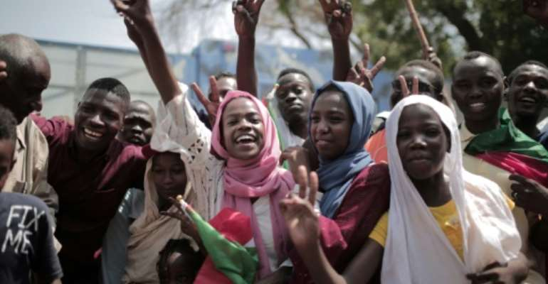 Sudanese citizens celebrate outside the Friendship Hall in Khartoum where generals and protest leaders on Saturday signed a historic transitional constitution meant to pave the way for civilian rule.  By Jean Marc MOJON (AFP)