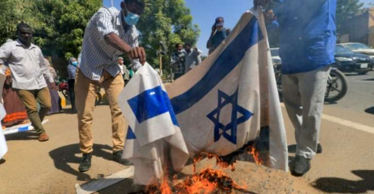Sudanese demonstrators burned an Israeli flag during a rally against their country's recent signing of a deal on normalising relations with the Jewish state.  By ASHRAF SHAZLY (AFP)